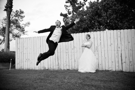 Groom jumps for joy in front as his beautiful bride wathes in amusement at their Alta Vista County Club Wedding Reception in Orange County, California