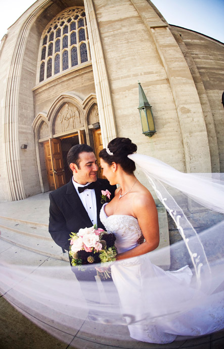 Bride and Groom and bridal veil blowing in the wind just after Catholic Wedding Ceremony in Los Angeles, California.