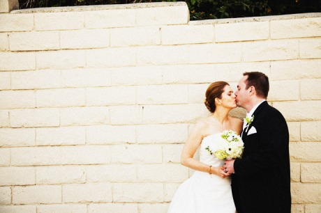 Bride and Groom stop to kiss on the path leading down to a Palos Verdes Beach after their La Venta Inn Wedding