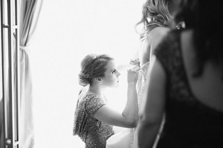 bridesmaid helps bride getting ready